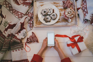Woman using smartphone for browsing internet store at home. Online shopping conceptspace for text. Mood winter. Seasonal holidays. Merry Christmas and New Year. Top view. Toned image. Selective focus.