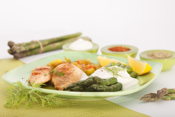 Roasted chicken breast meat and grilled asparagus with sauce on green plate. Asparagus meal decorated with lemon and dill.