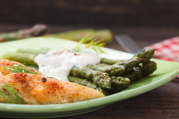 Roasted chicken breast meat and asparagus with sauce on green plate. Asparagus meal decorated with lemon and dill. Homemade cuisine. Close up image, wooden background.