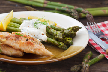 Roasted chicken breast meat and asparagus with sauce on green plate. Asparagus meal decorated with lemon and dill. Homemade cuisine.