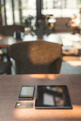 Modern digital smartphone and tablet computer with credit card lying on wooden table in cafe