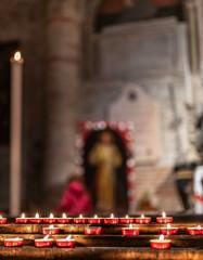 Candele e lumini di devozione e preghiera dei fedeli sullo sfondo di un altare sacro di una chiesa, con immagini sacre e di santi in preghiera