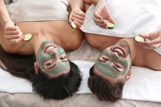 Happy couple enjoying facial treatment procedure in spa salon, above view