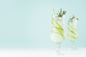 Juicy sour cold cocktails with ice cubes, cucumber, rosemary, straw in wet glasses on white wood board and light pastel green background, copy space. Wall mural