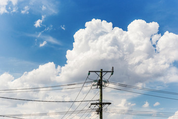 Cloudscape building behind electricity pylon on beautiful summers day.