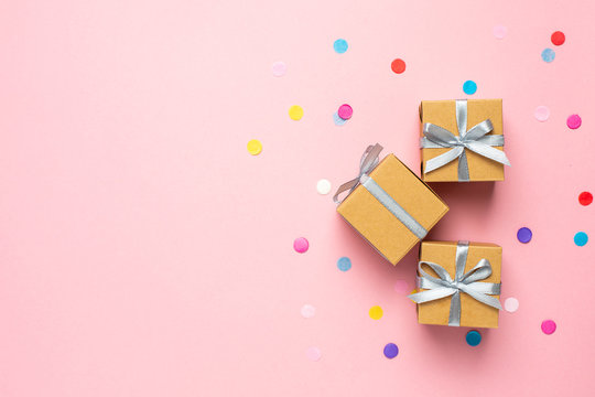 Gift or present box and color confetti on pink table with space for text. Composition for birthday, mother day or wedding