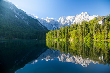 Beautiful morning scene with alpine peaks reflecting in tranquil mountain lake Wall mural