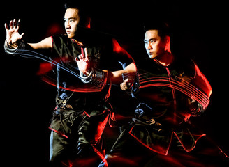 Wall Murals Music Band whushu chinese boxing kung fu Hung Gar fighter isolated man isolated on black background with speed light painting effect motion blur