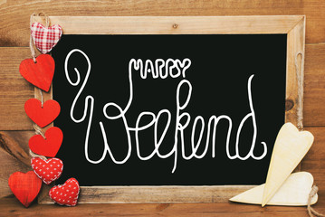 Chalkboard With English Calligraphy Happy Weekend. Red Textile And Wooden Yellow Hearts. Wooden Background With Vintage, Rustic Or Retro Style.