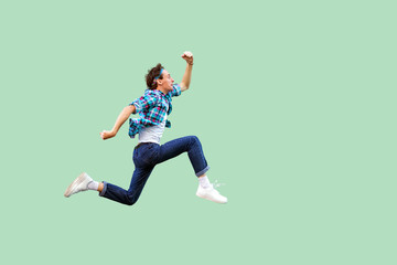 Jump to the success. Full length profile side view of active young man in casual blue checkered shirt and headband running very fast or jumping. indoor studio shot, isolated on green background. Fototapete