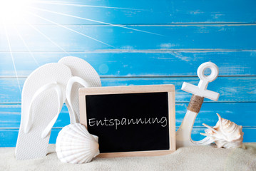 Chalkboard With German Text Entspannung Means Relaxation. Blue Wooden Background. Sunny Summer Card With Holiday Greetings. Beach Vacation Symbolized By Sand, Flip Flops, Anchor And Shell.