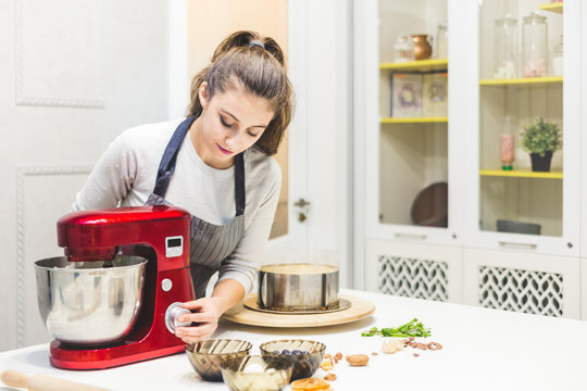 Young female confectioner whips cream in a metal bowl in a red electric mixer. The concept of homemade pastry, cooking.