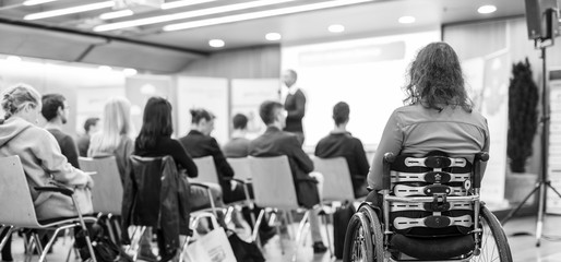 Rear view of unrecognizable woman on wheelchair participating in business conference talk. Business and entrepreneurship symposium. Black and white image.