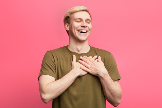 Happy positive man with closed eyes expresses his gratitude and thanks, keeps hands on heart.fair-haired man laughing at somebody. happiness concept