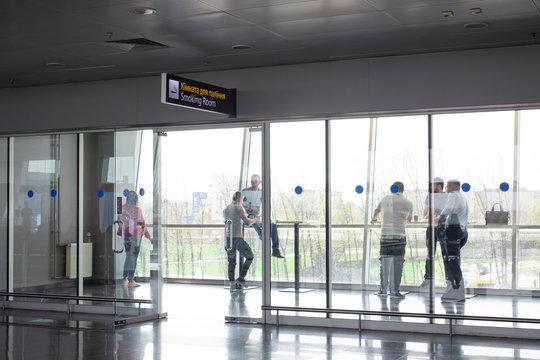 People in smoking room at international airport. Smoking sign on english and ukrainian.