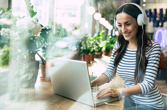 Young beautiful happy woman in headphones is listening music on laptop in cafe or co working center