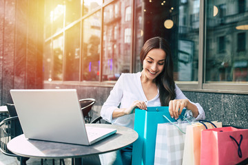 Happy attractive young smiling woman looking in shopping bags after mall outdoor
