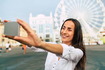 Beautiful happy modern cute woman makes selfie photo on her smartphone on urban city background