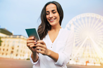 Cute beautiful young happy woman using smartphone on city background