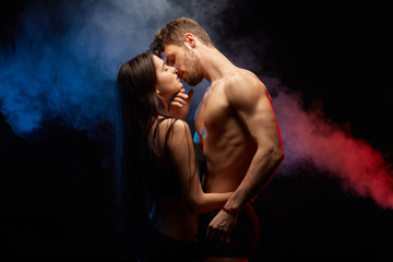 passionate couple kissing while standing face to face, isolated on black background.