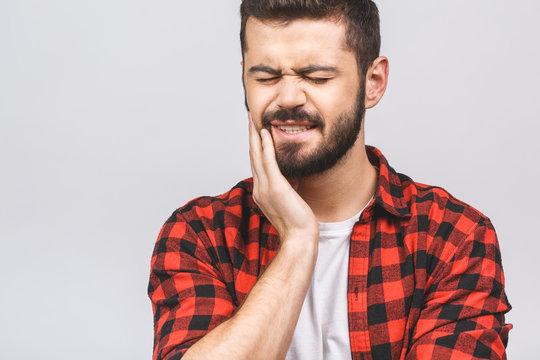 Close up portrait of nervous unhappy troubled handsome bearded man touching his cheek he has toothache isolated on white background copy-space.