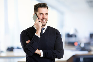 Businessman standing in the office and talking with somebody on his mobile phone