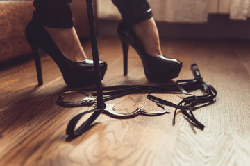 woman black high heels and sex toys. Sexy woman fetish pumps and whip, bdsm concept