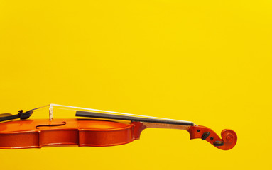 Classical music concert poster with orange color violin on yellow background with copy space for...