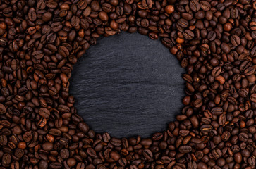 Frame made of roasted coffee beans on black table, top view