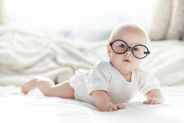 A newborn baby is lying on a soft bed in glasses.