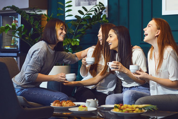 Young laughing women having tea party