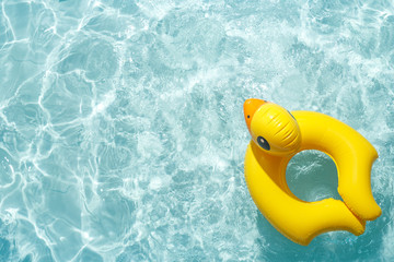 Inflatable float rubber ring in the shape of a yellow duckling in blue pool water.