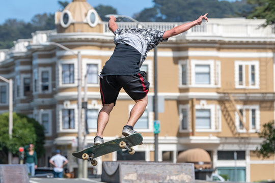 A skate boarder flies off the ramp at the Stanyan Skatepark in San Francisco near the end of Haight Street.  Victorian buildings in the background.  Sunny day.