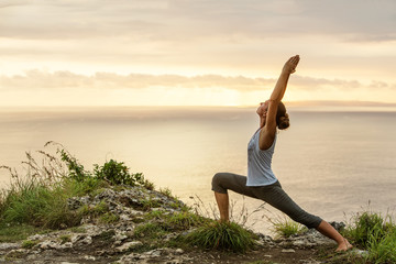 Fotobehang School de yoga Caucasian woman practicing yoga at seashore