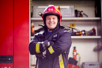 Image of happy male firefighter in helmet on background of fire truck