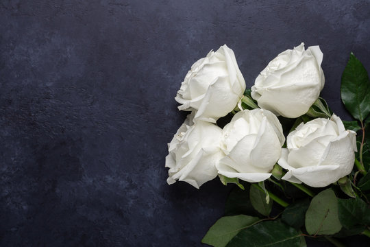 White rose flowers bouquet on black stone background