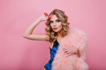 Close-up portrait of attractive elegant girl with curly hairstyle, posing dramatically and holding fluffy coat. Adorable young woman with beautiful make-up and red manicure standing on pink backround
