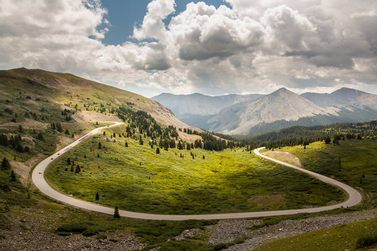 Large curving bend on road climbing to top of Cottonwood Pass in Colorado as sports cars race to summit