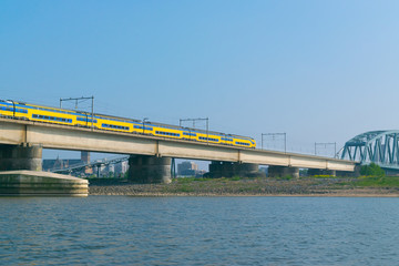 Dutch passenger train passing a bridge