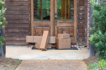 Shipping Packages on front porch of house, in front of the door.