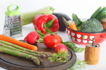 Mixed healthy vegetables on kitchen table and in the pot. Various colorful veggies, vegetarian meal ingredients