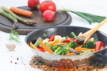 Roasted vegetables in a frying pan on white kitchen table. Vegetarian, healthy food.