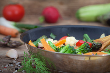Roasted vegetables in a frying pan on wooden boards. Healthy vegetarian food.