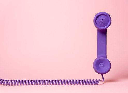 Retro telephone handset on a pink background