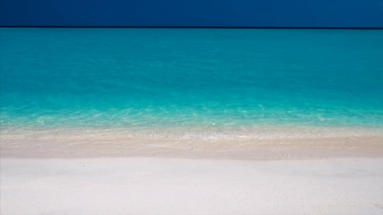 Wall Mural - Maldivian resort with calm turquoise sea, blue sky and pure white sand beach. Hand held camera