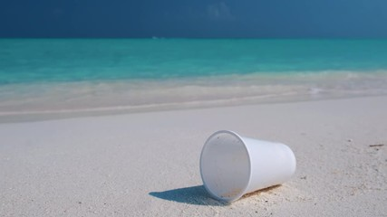 Wall Mural - White plastic cap lies on the perfect sandy beach. Plastic trash pollutes the pristine sea and the tropical beach