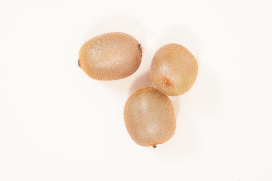 three oval kiwi fruit on a light background