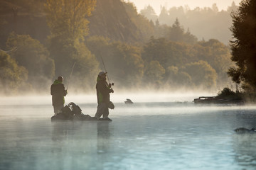 Photo sur Plexiglas Peche Men fishing in river with fly rod during summer morning.