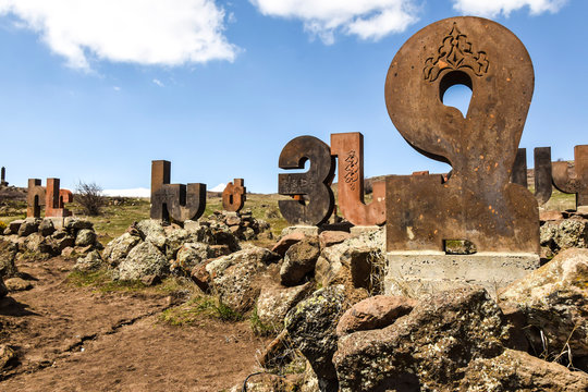 monument statue alphabet letters made of stone standing on  rocks on the nature of abstraction