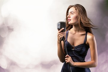 Young woman singing with microphone on blurred background Fotobehang